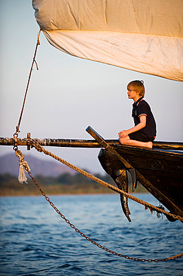 Young boy enjoys a trip on Lake  Lake Malawi on board the traditional dhow from Pumulani Lodge - p6521859 by John Warburton-Lee