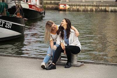 Freundinnen sitzen auf einem Pier an der Elbe - p788m2128519 von Lisa Krechting