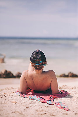 Rear view of woman reclining on beach looking out at sea, Angochi, Aruba, Lesser Antilles - p924m1468661 by Celeste Martearena