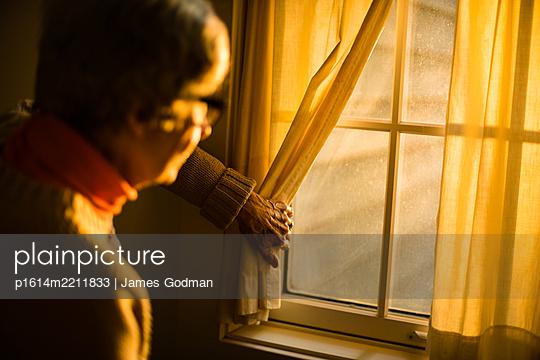 Ältere Frau schaut aus dem Fenster - p1614m2211833 von James Godman