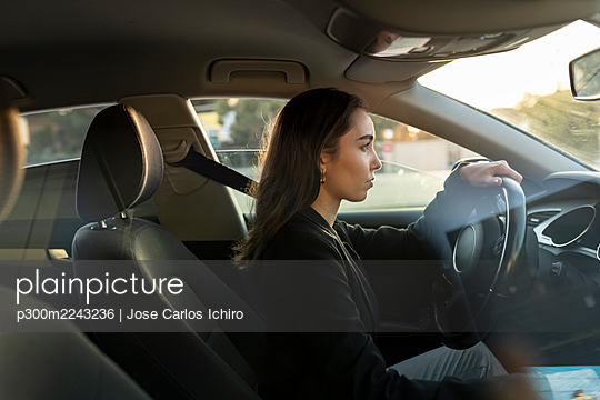 Young businesswoman looking away while driving car - p300m2243236 by Jose Carlos Ichiro