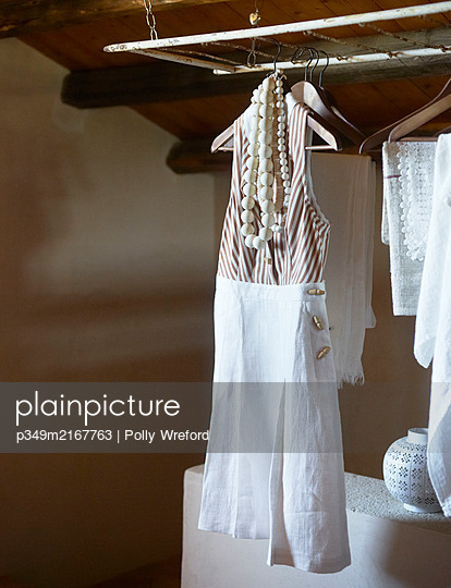 Summer dress and necklaces on wooden hanger in Sicilian home - p349m2167763 by Polly Wreford