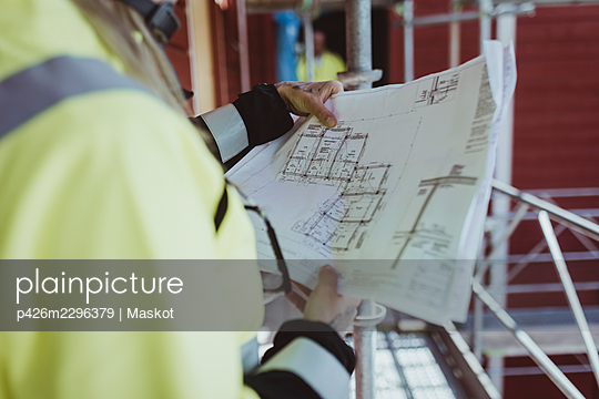 Female building contractor reading floor plan at construction site - p426m2296379 by Maskot