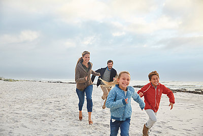 Playful family running on winter beach - p1023m1217925 by Ryan Lees