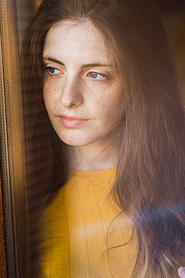 Portrait of pensive young woman with long brown hair looking out of window - p300m1581027 by Kike Arnaiz