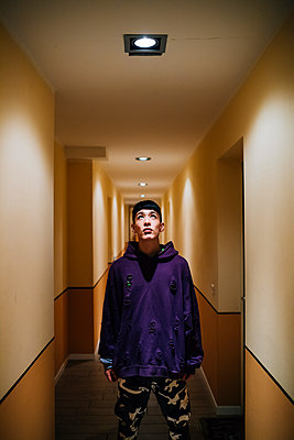 Young man looking at illuminated lighting equipment on ceiling in corridor - p300m2198635 by Eugenio Marongiu