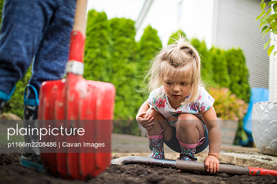 Cute young girl inspects dirt, looking for bugs and worms. - p1166m2208486 by Cavan Images
