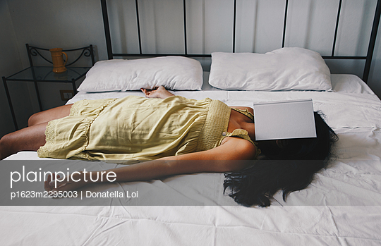 Girl rests on the bed with book - p1623m2295003 by Donatella Loi