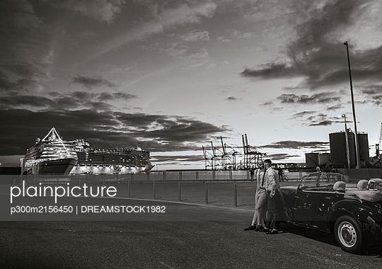Elegant gay couple at a vintage convertible car at the coast at sunset - p300m2156450 by DREAMSTOCK1982