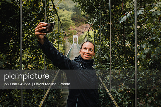 Smiling woman taking selfie with smart phone while standing on suspension bridge in forest - p300m2242331 by David Molina Grande