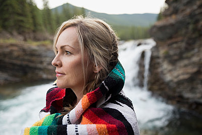 Pensive blonde woman wrapped in blanket looking away near waterfall - p1192m1183750 by Hero Images