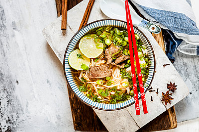 Bowl of Vietnamese Pho with rice noodles, mung beans, cilantro, spring onions and limes - p300m2104383 by Susan Brooks-Dammann