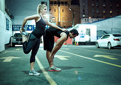 Couple doing stretching exercise during night on road in city - p300m2264631 by LOUIS CHRISTIAN