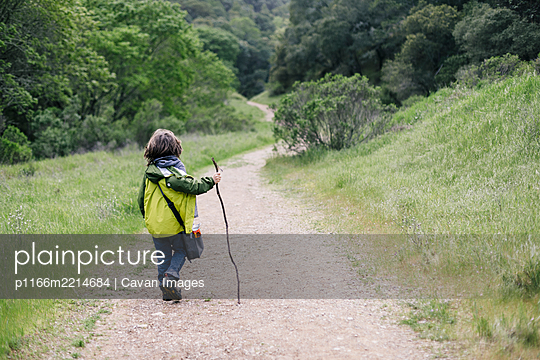 Back view of child walking stick by path trail in nature - p1166m2214684 by Cavan Images
