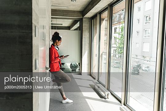 Young woman with headphones standing in corridor, using digital tablet - p300m2005313 von Uwe Umstätter