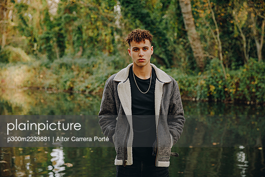 Young man with hands in pockets standing against lake - p300m2239881 by Aitor Carrera Porté