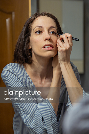 Woman standing in front of mirror, applying makeup - p429m2213492 by Costantino Costa