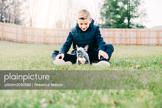 Boy playing with puppy on grass - p924m2090588 by Rebecca Nelson