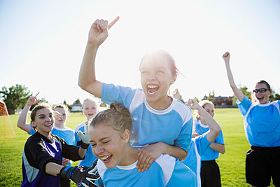 Exuberant middle school girl soccer team celebrating and cheering on sunny field - p1192m1173900 by Hero Images