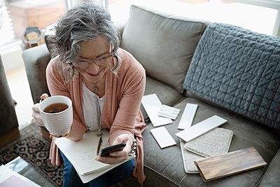 Senior female interior designer working on living room sofa - p1192m2088253 by Hero Images