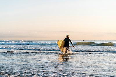 Happy woman walking with paddleboard on Mediterranean Sea at dawn - p300m2226111 by Ezequiel Giménez