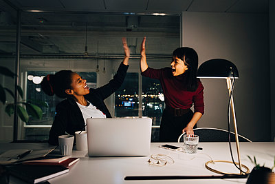 Cheerful female entrepreneurs giving high-five while working late in office - p426m2194718 by Maskot