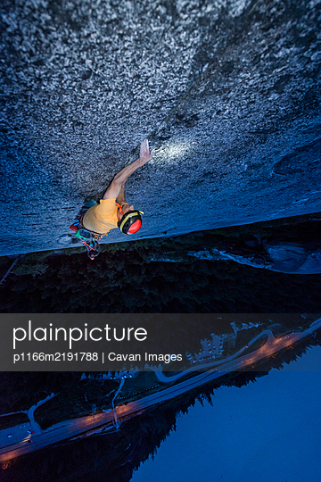 Top view man rock climbing at night above the sea and highway - p1166m2191788 by Cavan Images