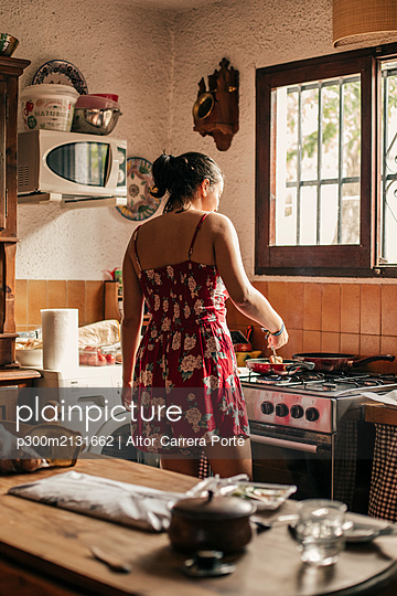 Rear view of woman cooking in kitchen using a pan - p300m2131662 by Aitor Carrera Porté