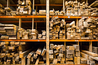 Large selection of wooden planks stacked on shelves in a warehouse. - p1100m1575728 by Mint Images