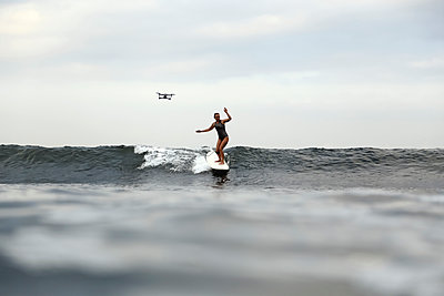 Woman on surfboard riding a wave - p1108m2210785 by trubavin