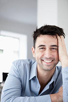 Businessman in office, smiling, portrait - p3008900f by Julian Rupp