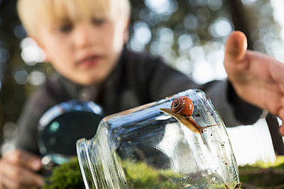 Snail on a glass with little boy in the background - p300m998151f by Philipp Dimitri