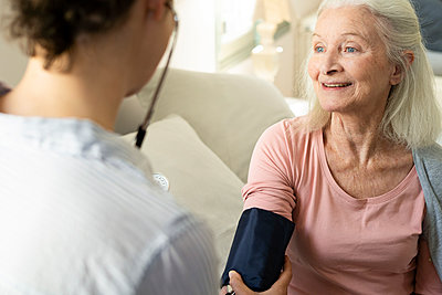 Home carer checking blood pressure of senior woman - p623m2165303 by Frederic Cirou
