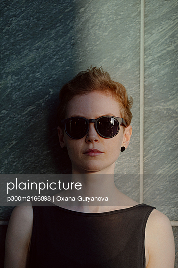 Red-haired woman with sunglasses, leaning on wall, portrait - p300m2166898 by Oxana Guryanova
