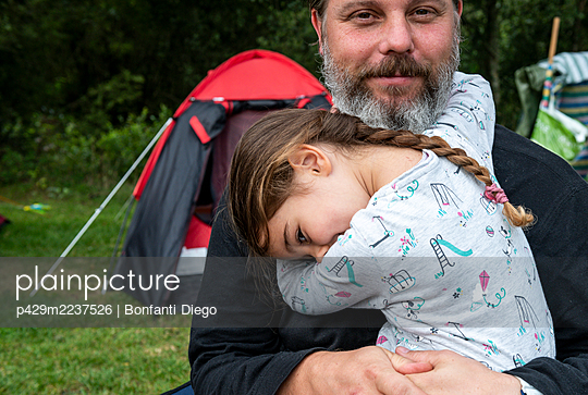 Father hugging daughter at camp site - p429m2237526 by Bonfanti Diego