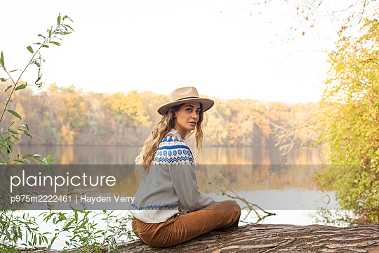 Young woman with hat sits on the lakefront - p975m2222461 by Hayden Verry