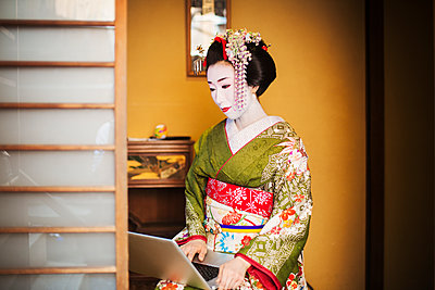 A woman dressed in the traditional geisha style, wearing a kimono and obi, with an elaborate hairstyle and floral hair clips, with white face makeup with bright red lips and dark eyes using a laptop computer.  - p1100m1185740 by Mint Images