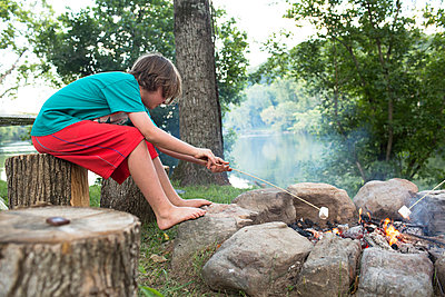Side view of boy roasting marshmallow over campfire while sitting on tree stump at campsite - p1166m1546382 by Cavan Social