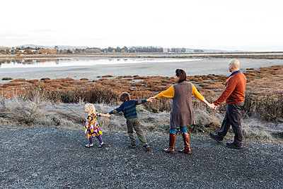 Back view of colorful family holding hands by natural park - p1166m2095119 by Cavan Images