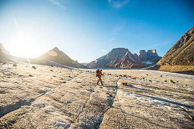 Backpacker exploring large glacier and mountains on Baffin Island. - p1166m2205812 by Cavan Images