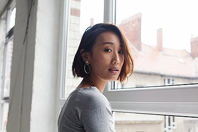 Seitliches Portrait einer modernen, asiatischen Frau vor einem Fenster  - p1301m2021056 von Delia Baum