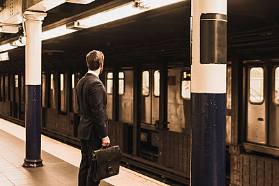 Young businessman waiting at metro station platform - p300m1192077 by Uwe Umstätter