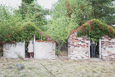 Bride and groom standing seperated in brick huts - p300m1204823 by Anke Scheibe