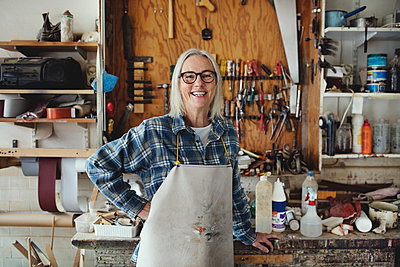 Portrait of smiling senior owner standing against tools at workshop - p426m1543028 by Maskot
