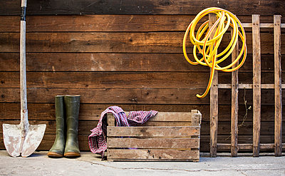 Row of spade, rubber boots and hosepipe by shed - p429m1175065 by Guido Cavallini