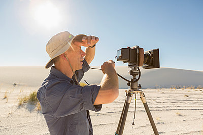 Caucasian photographer with tripod shielding eyes in desert - p555m1523053 by Marc Romanelli