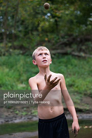 Junge wirft Sandkugel in die Luft - p1169m2016021 von Tytia Habing