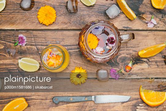 Refreshing mineral water with edible flowers, Viola wittrockiana, Dianthus caryophyllus, Calendula officinalis, lemon and orange - p300m1581686 von skabarcat