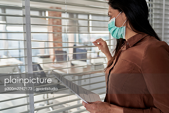 Female professional looking through blinds while holding document in office during pandemic - p300m2242173 by gpointstudio