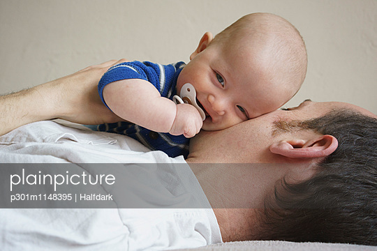 Close-up of father holding son while lying on bed at home - p301m1148395 by Halfdark